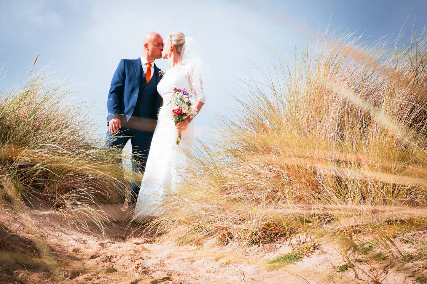 A bride and groom kiss on the sand dunes at Crantock Beach in Cornwall.